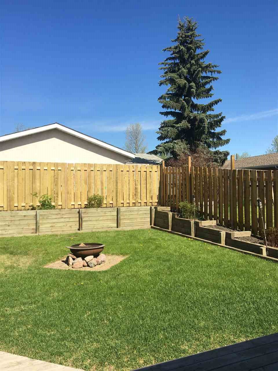 The back yard was leveled out to make the space more useable. Wooden planters around the yard allow you to decide... flowers or vegetables? The low deck is extensive to hold your yard furniture.