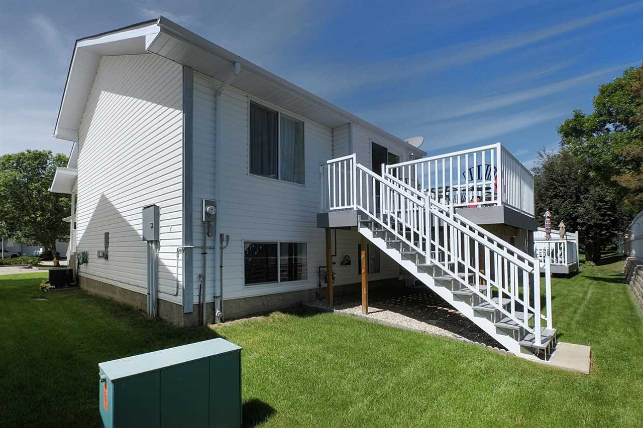 The back raised deck has stairs to lead down to the back grassed area.