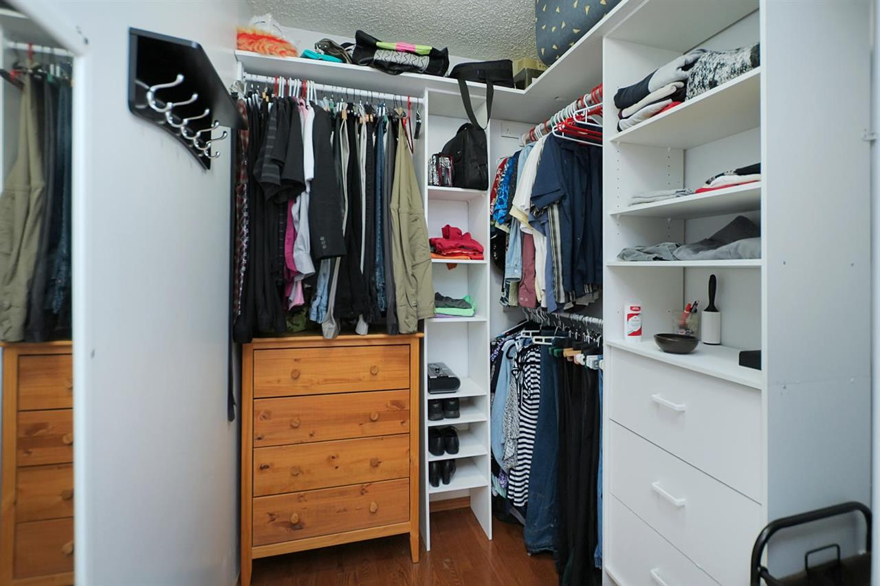 The walk in closet is large and well organized with shelving and some drawers.