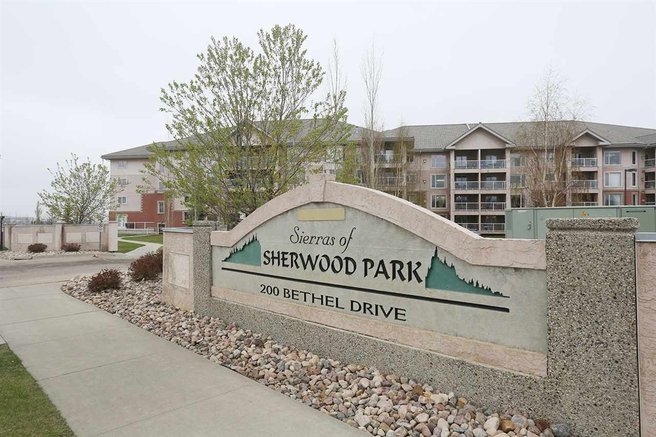 """Welcome to Sierra's Of Sherwood Park! This professionally renovated two bedroom, two bathroom unit is located on the top floor with great west-facing views. With over 1065 sq.ft., an open floor plan, bright color palette and 9' ceilings, the unit has a welcoming flow with great natural light. The flooring throughout is a wide-plank handscraped White Oak hardwood, with complimenting 12x24"""" ceramic tile in the bathroom and laundry areas. The kitchen is a culinary dream with Kitchencraft cabinetry, Quartz countertops, Samsung S/S appliances, and an oversized eating bar. The laundry room, dining area, and second bedroom also boast upgraded Kitchencraft cabinetry for even more storage. The bathrooms have new plumbing fixtures, flooring, lighting and paint. The living room has all new lighting, natural gas fireplace and patio door out to the oversized balcony with views! Complete the package with underground parking and storage, social rooms, pool, workshop, 4 guest suites, and condo fees include all utilities."""