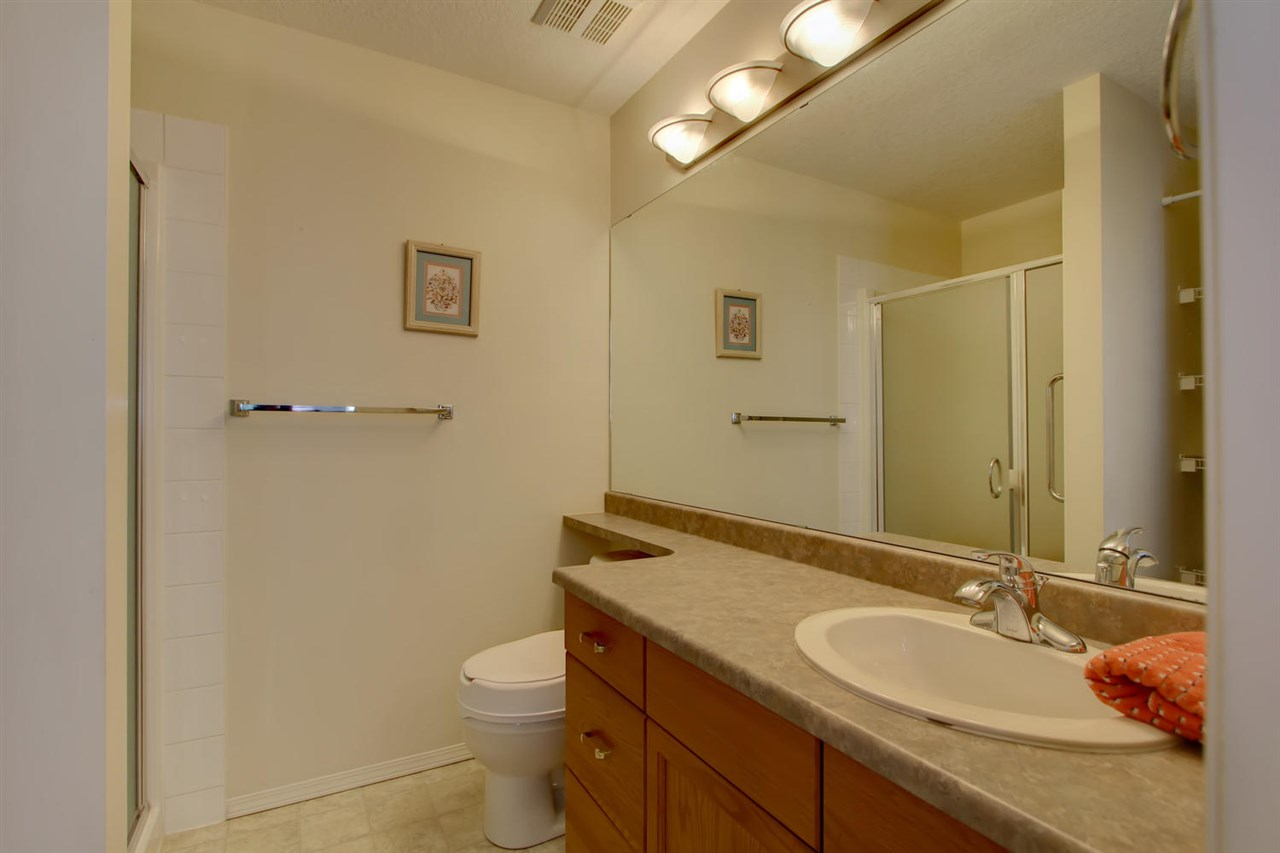 The en suite bathroom has a shower and extra storage on shelves behind the door and beside the shower stall.