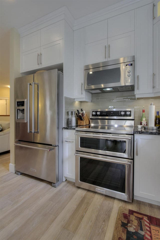 High end appliances include a high tech fridge and double oven stove.