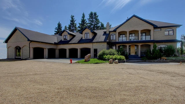 Private, luxurious estate home on 6.5 fenced acres within the Edmonton City limits. Gated entrance with tree lined drive leads to this executive 2 storey custom-built home plus a 6400 sq. ft. ultimate office/shop/3 bay work area. Over 6500 sq. ft. of living space with a raised Great Room featuring a slate gas fireplace, English maple floors, glass block & column detailing & is open to the spacious gourmet kitchen boasting 14' granite cooking island w/grilling station & raised eating bar, custom maple cabinetry & built-in S/S appliances. The breakfast nook has access to the patio & yard. The upper level features a bonus room & spacious master suite w/double-sided gas fireplace & 5-piciece ensuite & walk-in closet. The walkout lower level features a game room, wet bar, 4 additional bedrooms, family room w/gas fireplace & wine room.