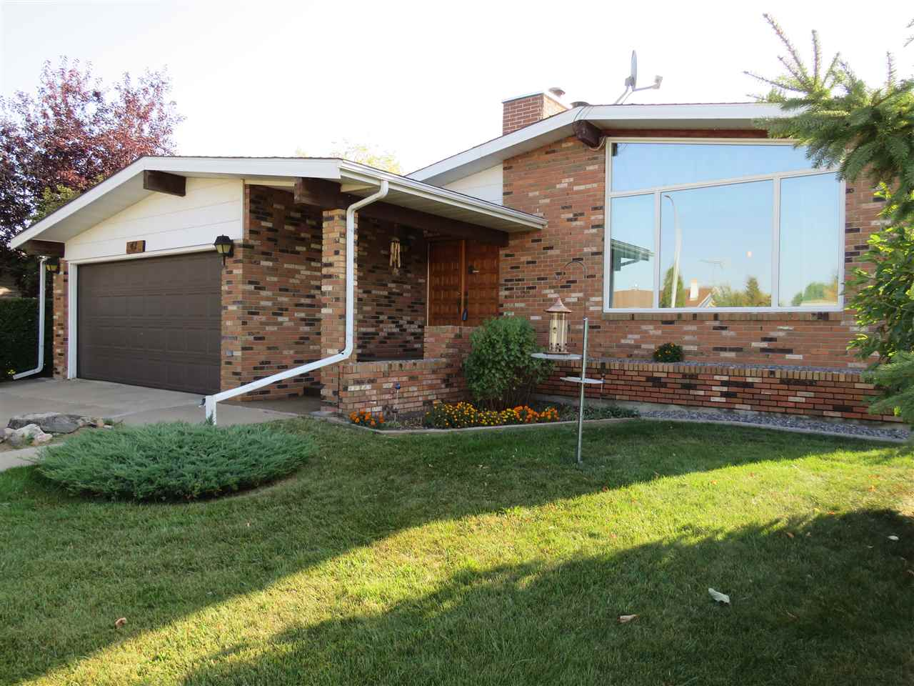 1978 custom built 1336 sq ft bungalow with a double attached garage situated on beautifully treed, meticulously manicured and maintained fenced, landscaped lot; located in the Town of Tofield. Very nice neighborhood and family home with both levels developed containing a total of 4 bedrooms (3 on main), 3 bathrooms and many other special features throughout. Including a functional and appealing open floor plan with a large kitchen and dinette area, formal dining room, living room with open beam ceiling and a custom built brick faced wood burning fireplace, large main floor laundry room (new flooring 2017) with access to the attached garage and the 10x16 attached sun room. Lower level contains a large family room with free standing fireplace, bar area, additional bedroom and bathroom, and ample storage throughout. Attractive curb appeal features a brick front facing exterior, chain link fencing, 2 storage sheds (1 used as kid?s playhouse); all this plus central air conditioning. Excellent family home.