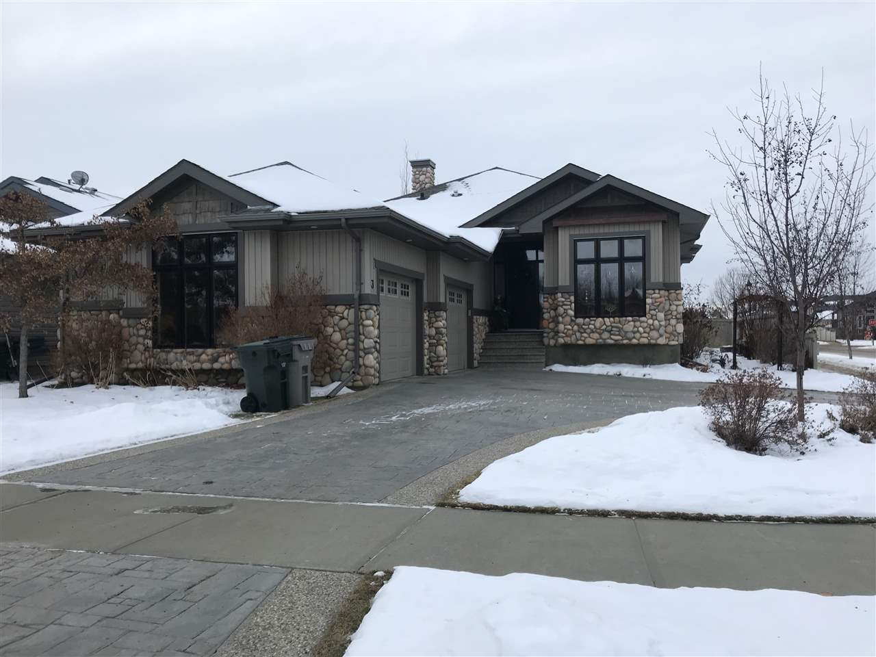 Beautiful, Custom built bungalow displaying attention to detail in the desireable location of Willow Park, Stony Plain, close to walking trails has stunning curb appeal including exposed aggregate, stamped concrete, copper and river rock detail and oversized, heated 27x22 garage. Over 3000sqft of living space encompasses the finer details and quality craftsmanship including transoms above doorways on the main, grand pillar detail, wainscotting, crown moulding and custom cabinetry from the library to the laundry room to the wine cellar. The great room boasts 12ft ceilings, custom fireplace & mantel and adjoins the colossal dining room and kitchen with pillar detail creating a sense of separation. Kitchen displays granite, S/S appliances, farm style sink, and walk through pantry to the laundry room. Master retreat has garden door opening to a covered deck and ensuite that boasts dual sinks, steam shower, jacuzzi and w/i closet. Basement has 2 large bdrms, great room, wet bar, wine cellar, and infloor heat.