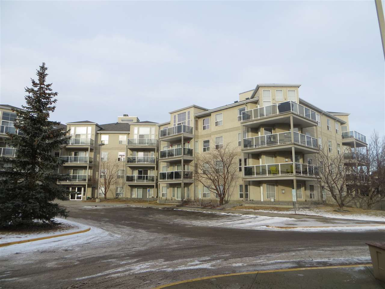 Corner unit with wrap around balcony! Enjoy morning coffees on the spacious balcony of this well priced larger 3rd floor unit featuring 960 sq ft.  Laminate and tile flooring welcome you into the home. The well designed kitchen is a good size with island eating bar, double sink, plus ample cabinets and counter space. There are two bedrooms, 2 bathrooms that both feature showers, closet organizers, air conditioning, gas fireplace, laundry area with some storage plus another storage cage downstairs in front of your underground parking stall (#222) that is titled.  Heated stall is located in a good location only a few steps from the elevator, plus the underground parking has a car wash!  The complex is located in convenient Terra Losa, close to shopping, transit and churches, plus the trails at the lake are nearby.