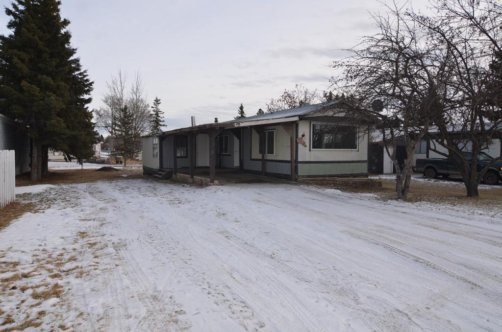 AFFORDABLE PROPERTY and great starter. 1056 sq ft mobile home with covered carport/deck and its own 52'x140' lot. 2 bedrooms along with 4 piece bath. Large living room open to kitchen and dining. Excellent front porch addition spacious and flexible for multiple uses. All appliances included as well as Laundry. Recent vinyl window upgrade as well as updated flooring. Hassle free Metal clad roof. Large yard with back alley access. Good modern yard shed. Why rent when you can own for the same price. Come take a look and see how easy it can be.