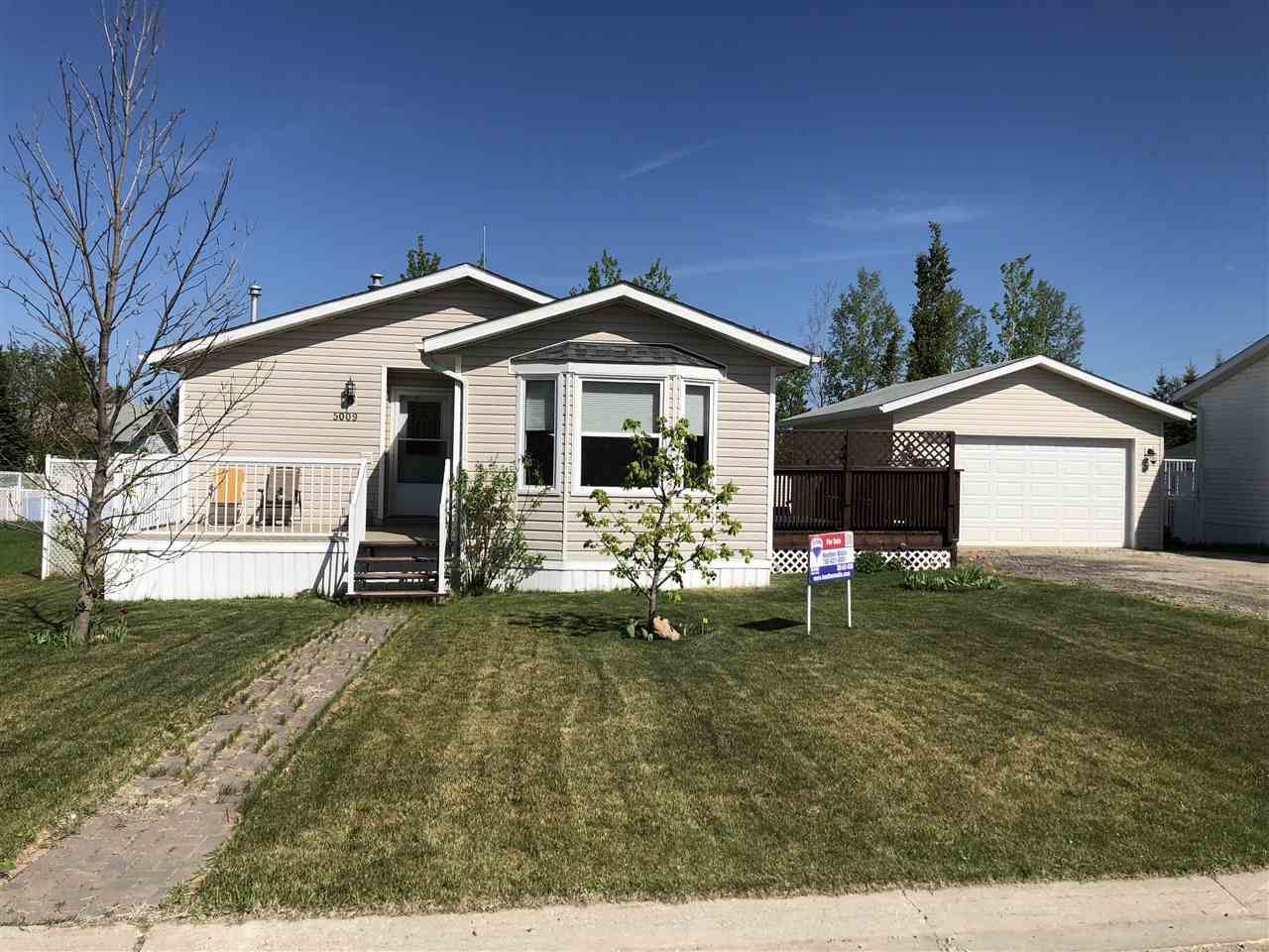 A beautiful home showing pride of ownership. Enjoy having an extra large fenced yard with lots of room. It's like being on an acreage with all the amenities of town. A true modular home measuring 28 feet wide. The kitchen, dining area & living room has access through the double garden doors to a two tier deck, the back yard, & the oversized heated garage. The kitchen has a pantry, island & is nice & bright for the chef of the family. The laundry room comes with extra cabinets, & storage closet There is a beautifully landscaped yard with a mature apple tree, container gardening, oversized shed, green house, barbeque area, & still lots of room to play. New Shingles 2016. Rocky Rapids is a bedroom community to Drayton Valley. It has it's own store, gas station, community hall & playground & is minutes to the golf course, ski hill, cross country skiing, North Saskatchewan River, ATV trails, & walking trails to the River & a pedestrian path to Drayton Valley. COUNTRY LIFE WITH TOWN CONVENIENCES. MUST SEE!