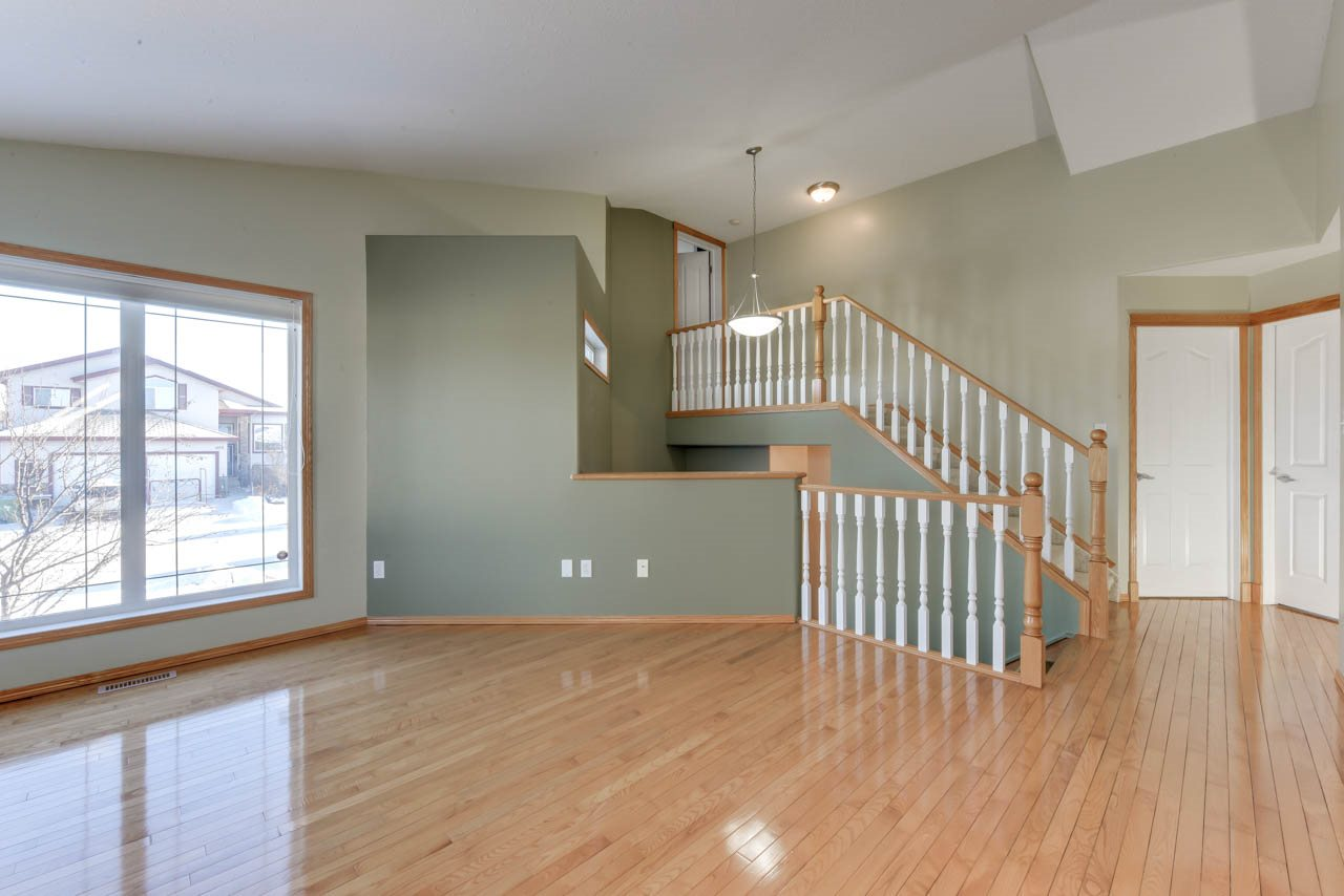 This beautiful WALKOUT Bilevel in Beaumont is a MUST SEE! Perfect location with a WEST FACING backyard, path leading to Four Seasons Park, the Aqua-fit Centre, and Schools also nearby. This bright and spacious home boasts NEW VINYL SIDING, EXTRA WINDOWS on the corner lot, VAULTED CEILINGS, Gleaming HARDWOOD on the main floor, and TILE in the bathrooms and front entrance. There are 3 bedrooms on the main level, including the Master Bedroom which has a Vaulted Ceiling . You can also access the Walk in Closet from the Ensuite. A  4th BEDROOM can be found above the garage. The beautiful Kitchen offers bright WHITE CABINETS, POT AND PAN DRAWERS, TILE BACKSPLASH, RAISED EATING BAR. You will also find the Dining area and sliding doors leading to the DECK, where you can enjoy those hot Summer evenings. The DEVELOPED WALKOUT BASEMENT has a 5th BEDROOM, a 4pc bath and huge REC AREA -great for a pool table! You can also access the CONCRETE PATIO and backyard. Such a great family home... you have to check it out!!