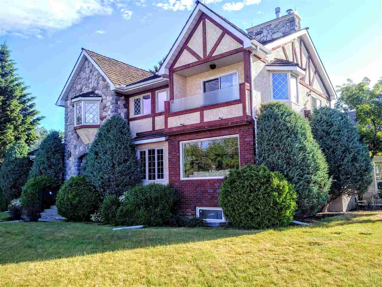 Undoubtedly one of Edmonton?s finest examples of Tudor-Revival architecture, this 2,981 sq ft masterpiece is among the rarefied lots that sit at the edge of the river valley while offering a full, breathtaking view of Edmonton?s skyline. One visit and you will see why Ada Boulevard is one of Edmonton?s premiere addresses. This 6 bdrm 2-storey actually sits on TWO lots, offering unmatched estate-style living near the downtown core. The main floor boasts 2 living rooms, a bedroom, formal dining room and a gourmet kitchen (featuring gas stove with brick surround, granite countertops, stainless steel appliances, dining nook and large island). Upstairs are 2 bedrooms and a palatial master that must be seen in person, with 2 walk-in closets, an ensuite (with separate tub/shower), a 3-sided fireplace, and 2 balconies offering spectacular views. The fully-finished basement features 2 additional bedrooms, a rec room and plenty of storage. An attached double garage and beautiful landscaping only add to the luxury.