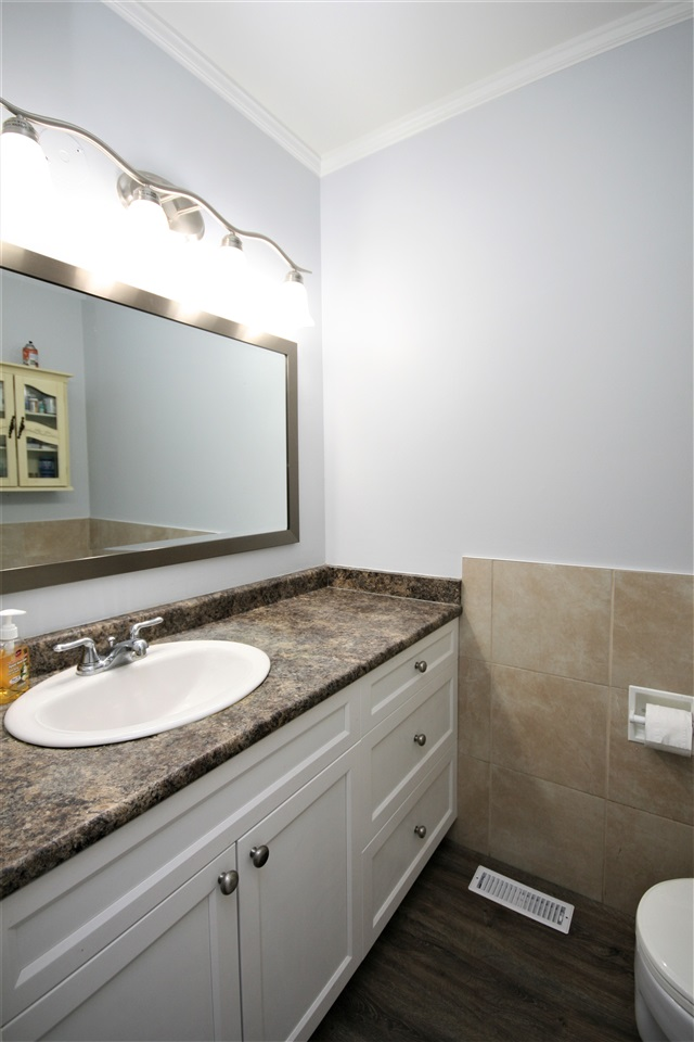 The main floor washroom has been upgraded with a newer extended vanity with lots of storage, fresh lighting, new flooring and tile accents.