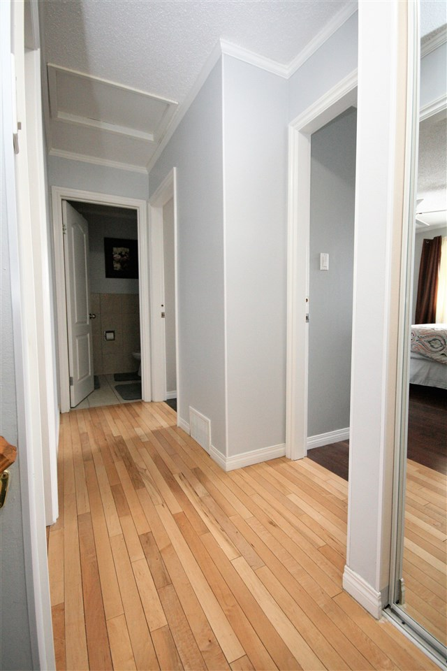 Hardwood floor extends from the stairs to the upper landing and into the bedrooms.