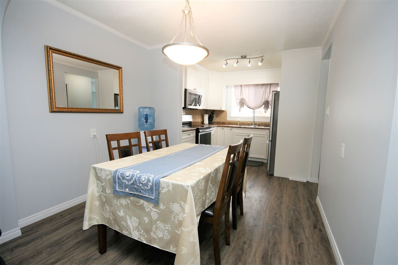 Spacious dining room with upgraded pendant light fixture and room to seat a large table of six.
