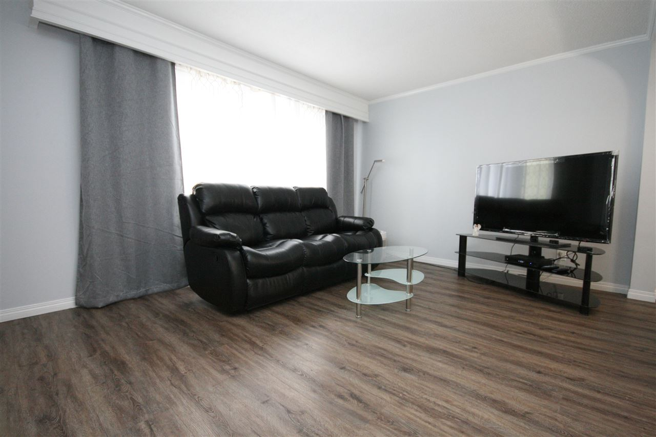 The sunny living room boasts a large, south facing window and vinyl plank flooring.