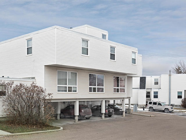 LOTS OF SPACE IN this 3 level town home with covered parking to keep the snow off!  The entry level has foyer but is mainly dedicated to a large storage room and laundry facilities, while the upper levels are all about family living!  Excellent layout with large eat in kitchen with new linoleum flooring, plenty of cupboards, 2 year old fridge.  The living area is spacious, stepping out onto a west facing patio and fenced yard.  There is also a main floor 1/2 bath with new lino, toilet and extra space for bathroom storage.  The upstairs has three bedrooms and a 4 piece bathroom.  The master includes a west facing balcony.  All the appliances are included.  Tucked away in the complex - so very quiet yet easy access to amenities, schools within walking distance, and close to major arteries.