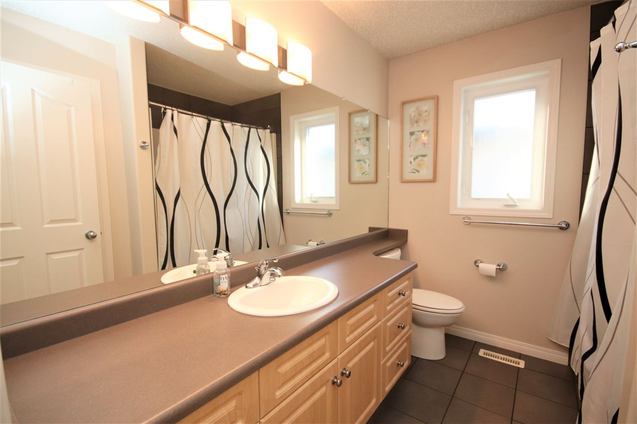 The main floor washroom has a huge vanity with extended countertop and mirror.
