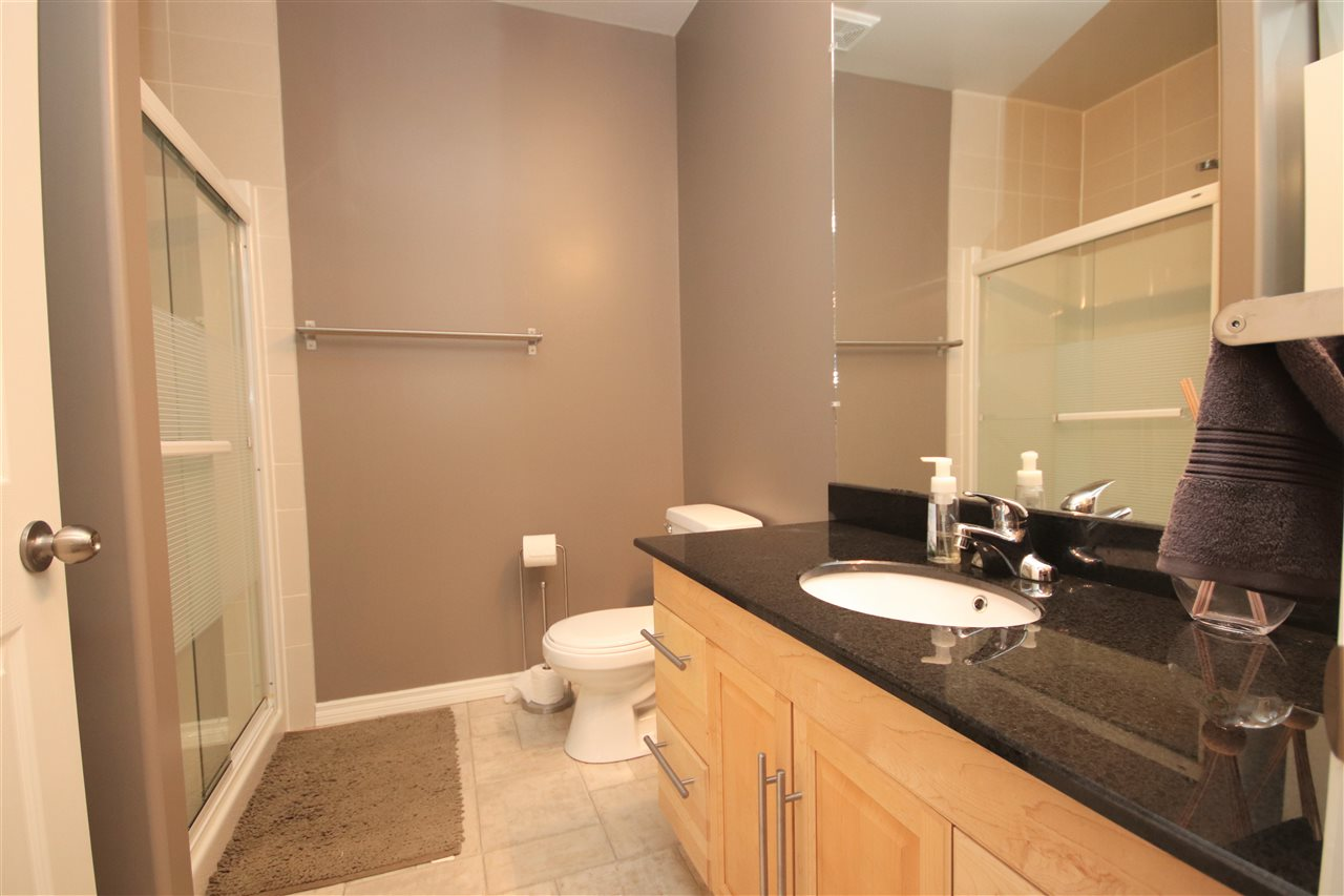 The basement bathroom has a large vanity with granite countertop and an undermount sink.