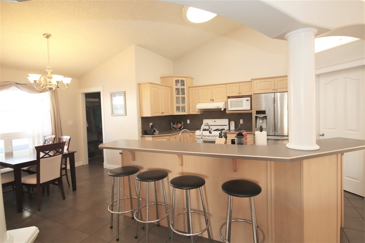 The open kitchen boasts high ceilings and a raised eating bar.