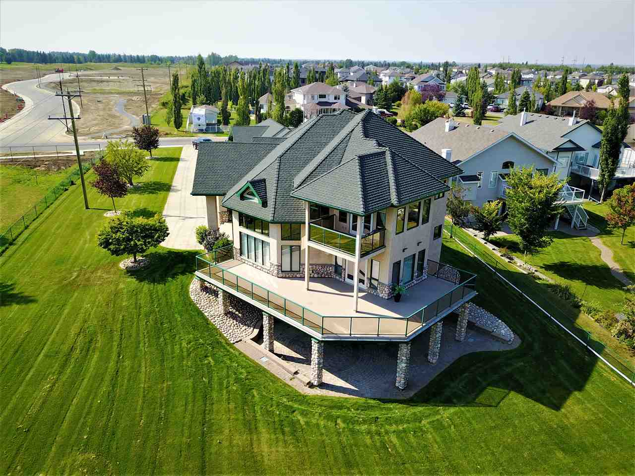 Amazing. With too many features to list this home will check off all the boxes on your wish list and more! 15 Briarwood Way is stunning and designed with distinction! Backing the 5th hole of the Stony Plain Golf Course with over 5500 sq ft of total luxury living space. The main floor features soaring ceilings, huge south facing windows, 3 sided gas fireplace, dining area & massive kitchen with 8 appliances! The custom curved staircase leads to the 2nd floor and French doors to your master retreat. Beauty awaits you in the massive 5pc en-suite with air jet tub, spacious sitting area & private balcony where you?ll frame the view of the golf course & park. The f/f walk-out basement features a wet-bar & gas fireplace. 4 bedrooms total, main floor den/office, AC, in-floor heat in garage & basement, electric blinds, built-in sound & much more! The 8 stall garage is gorgeous & features a drive-through overhead door, bathroom, & covered RV parking. See for yourself!