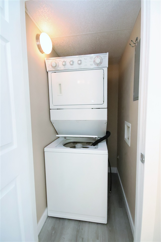 The in suite laundry room houses a stacked washer/dryer unit.