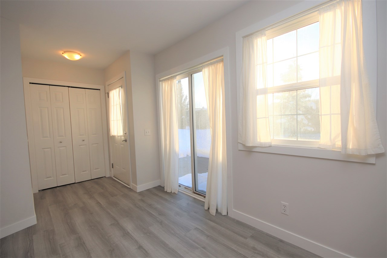 Grey, vinyl plank flooring extends from the front entry and through the entire unit.