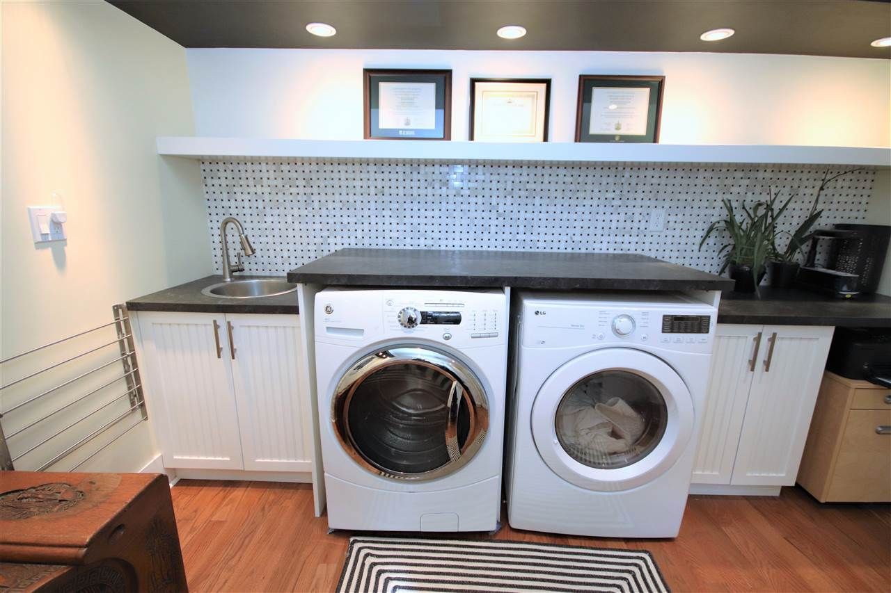 An organized laundry aread with front load washer and dryer, washing sink and additional storage.
