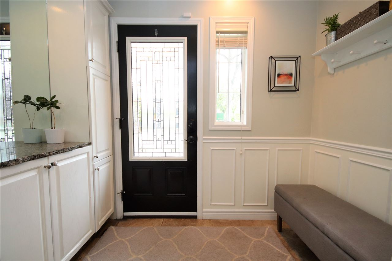 Welcome home.  This entry features a modern entry door with sidelight and wainscoting.