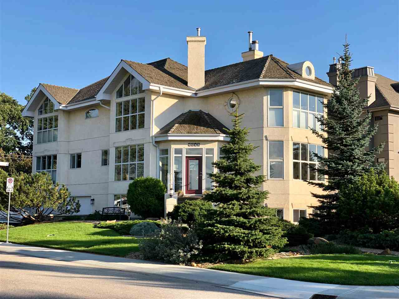 Beautifully designed two-story home located on Saskatchewan Dive in sought-after Windsor Park. Walk to the University of Alberta and hospitals. Fabulous views of the river valley and park reserve - lots of nature at your front door. Over 3,100 sq. feet above grade. There's a modernized gourmet's-delight kitchen with top-of-the-line appliances. A nook overlooks the spacious living room and formal dining room that are separated by a gas-lit, wood-burning fireplace. Stunning, curved staircase to upper level with three bedrooms and a flex room. Master bedroom has a gas fireplace. A glass curtain wall allows lots of natural light to permeate this home. There's an atrium, gorgeous landscaping, a hot tub on the Southeast deck, and an attached, heated, insulated, over-sized double garage with lots of storage.