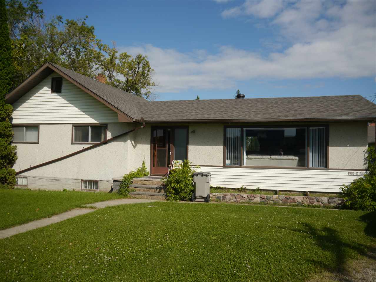 Two, 1 acre parcels, side by side. Zoned C3 Central mixed. 4907 is rented for $1,100 per month and is 1460 sq. feet and has 3 bedrooms and a two piece ensuite. It was built in 1951 but had a large addition done in the 80's. Tenants want to stay.  4911 is rented to a construction company for $2,000. per month and is 831 sq. ft and has a 4 pc bath. It was built in 1941 and has a few upgrades. Two single garages and large storage shed stay.  Endless possibilities for development. Homes and appliances as is where is. Floor area is for 4907. Smaller house is 831 sq. ft. Property has been approved in the past for a 92 suite apartment building with commercial frontage or 25 residential lots.  Invest now and build later.