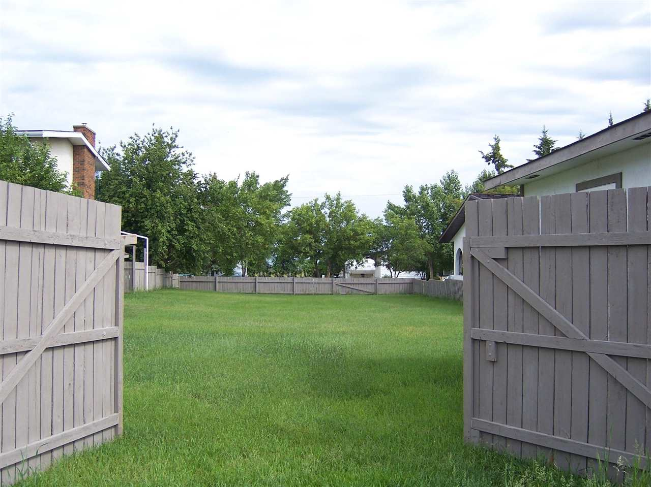 If you are looking for an affordable large lot to be able to build your future home on with back alley access look no further.  Close to the local hospital and all other services.  This lot has been maintained with grass and is completely fenced.