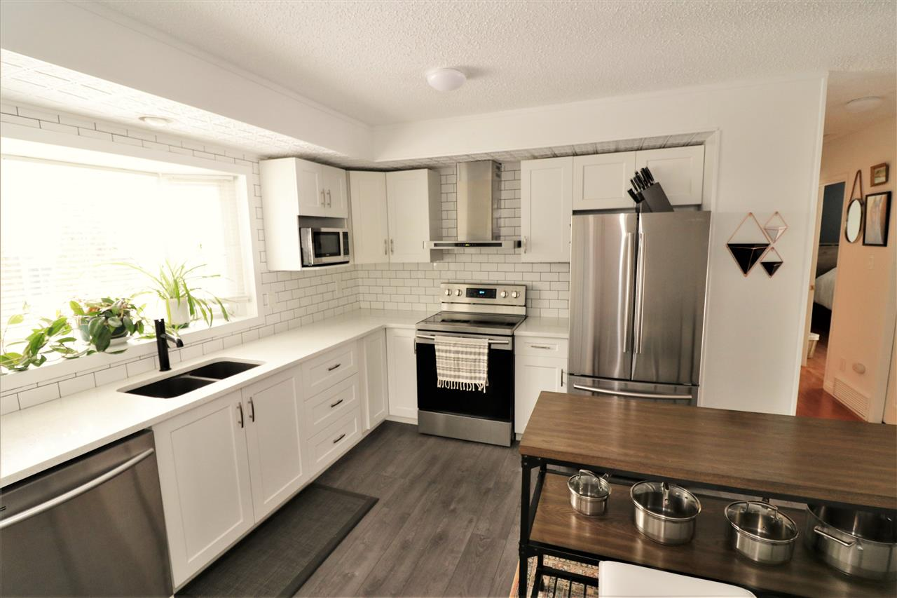 Gorgeous renovated bi-level on a quiet street in Lacombe Park. Big bright windows bringing in loads of natural light & a stunning modern kitchen set this home above the rest. Kitchen features white shaker cabinets, stainless steel appliances, wall mounted stainless range hood, white subway tiles, a central island & a large window over the sink looking to the huge backyard. Vinyl plank in the kitchen & beautiful hardwood through the rest of the main floor. Dining room, gorgeous living room off the front entrance, 2 large bedrooms & a full bathroom upstairs. Basement has another big bright living area, 2 more bedrooms & another full bath, with large windows looking above grade, the best part of a bi-level! Double detached garage & a huge pie shaped yard with an amazing outdoor brick fireplace. Great location surrounded by schools & parks. Newer shingles on the house, brand new furnace & hot water tank. Updates are done and ready for you to move in!