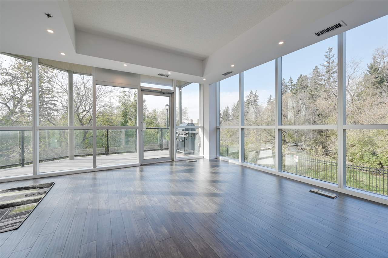 Ravine living awaits you with this stunning 1 bedroom 1.5 bath corner unit drawing nature inside with 10 ft floor to ceiling windows. One of 5 rare units in Trinity Pointe's concrete and steel modern tower. Extensive list of new (2019) custom kitchen with ultra modern flush profile cabinetry in linen grey, high end stainless steel built in appliances with countertop gas stove and wall mounted ovens. Imported glass tile backsplash and white quartz waterfall countertops complete this designer kitchen. New industrial lighting, custom backlit wall mounted gas fireplace, laminate floors and fresh crisp white paint throughout making this unit virtually brand new. The Master suite is a living dream to wake up to and features ample walk-in closet w/private ensuite bath, glass vessel vanity & 6ft soaker! Security Gate to titled private garage and visitor parking, large reserve fund, low condo fees and lenient pet policy make this a wise investment near major universities and vibrant Whyte Avenue/Millcreek Ravine.