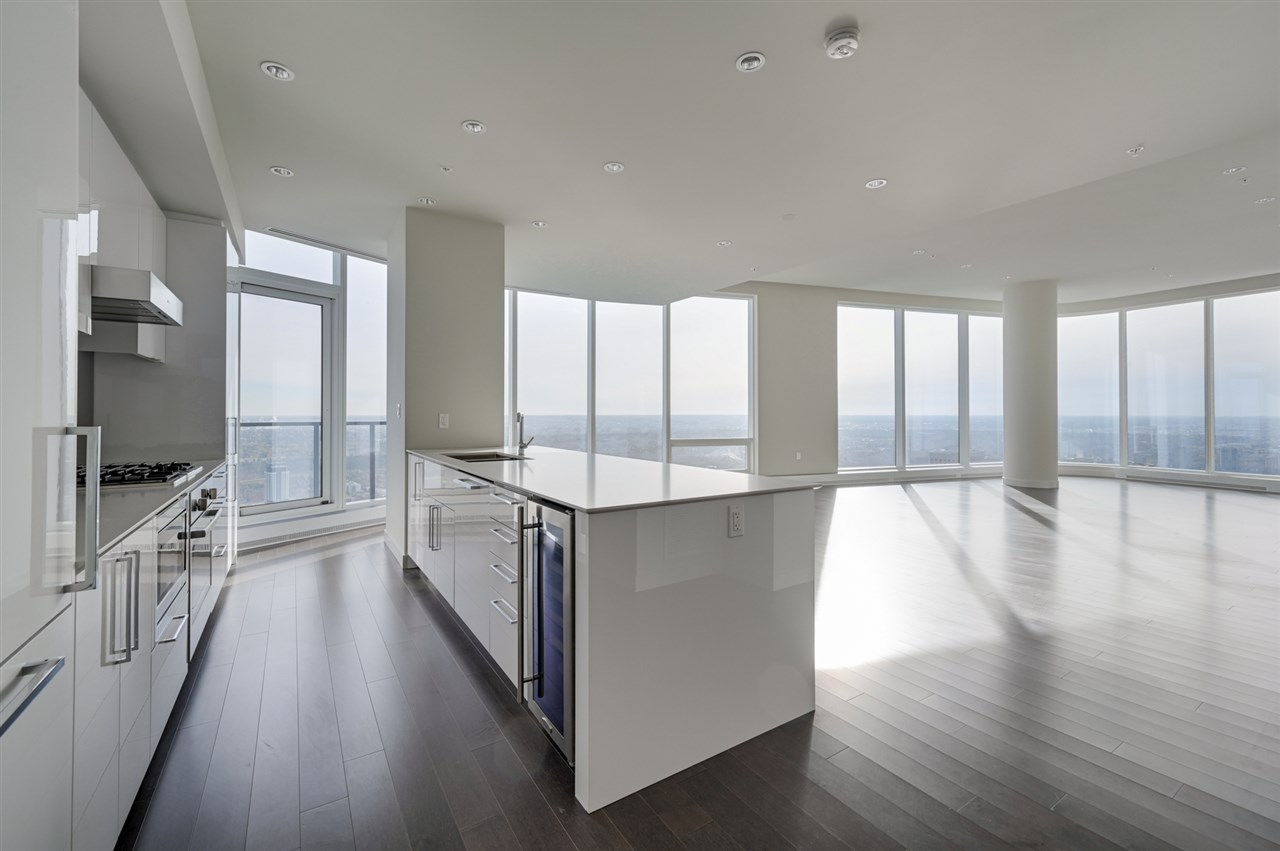Welcome to THE LEGENDS PRIVATE RESIDENCES, the pinnacle of condominium living in Edmonton.  Come & experience the stunning architecture, unmatched luxury lifestyle, high end finishes & this is just the beginning of what is to come in the ICE DISTRICT.  Only 3 units on the floor.  This 1993 sq.ft unit has 2 master bedrooms with ensuite bathrooms & a den & a 2 pce powder room.  SPECTACULAR RIVER VALLEY & DOWNTOWN VIEWS.  White cabinetry & quartz countertops throughout & espresso color hardwood flooring.  Linear electric f/p. 2 walk-in closets in the master bedroom, 5 pce ensuite w heated tile floors.  2nd bedroom with a walk-in closet & 4 pce bathroom w access to the south facing balcony.  East balcony off the kitchen.  Bosch & Miele appliance package.  A/C, 2 UNDERGROUND PARKING.  Condo fee includes access to the residence club (billiard lounge, conference room, lounge, rooftop patio, 24/7 concierge) + J.W. Marriott amenities: spa, pool, room service & Archetype Gym.  Access to DOWNTOWN PEDWAY SYSTEM.
