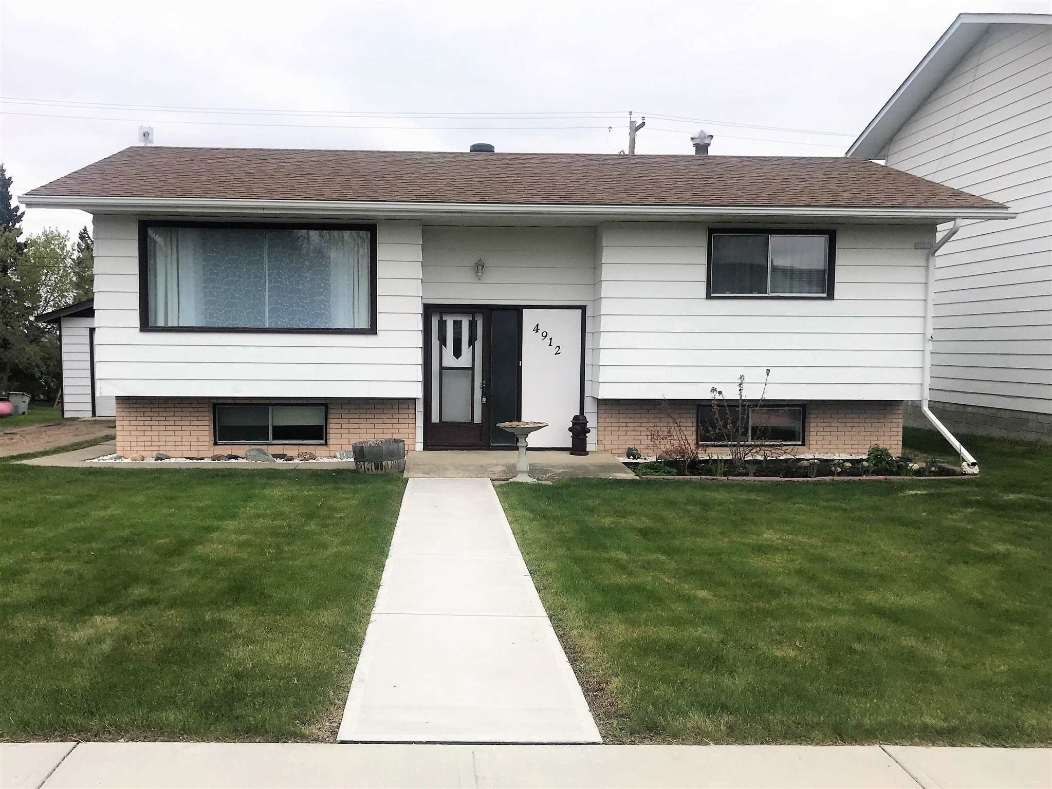 Family Home in Evansburg! Four bedrooms (2 up 2 down), two bathrooms, open kitchen/dining with plenty of cupboards / counter tops and a large living room with pellet stove for those cooler days. The basement adds a family room, bedrooms, bathroom, laundry and storage space. New roof and vents in 2020. Large fenced back yard backs onto alley and features a variety of fruit trees and shrubs, large 2 level deck, fire pit, chain link fence with privacy lattice and a 8x12 well built greenhouse. The front yard is maintenance free with a new wide sidewalk. Garage has a new insulated 8x10 door with remote, concrete floor, power and is insulated/drywalled. The long gravel driveway has lots of room for parking vehicles and/or RV.