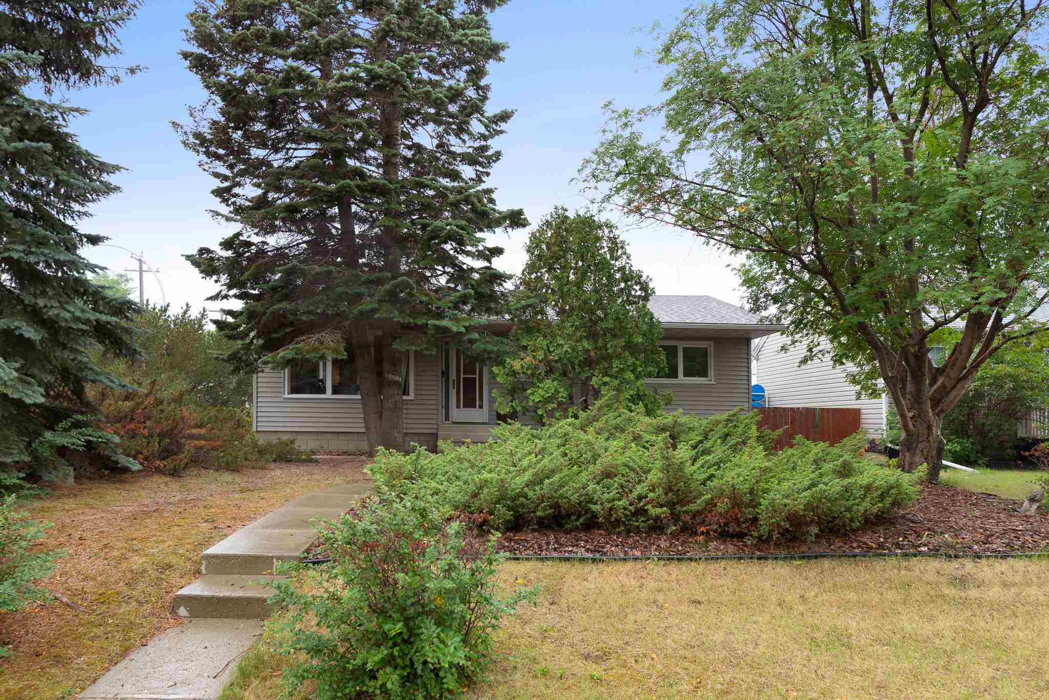 """Welcome to this classic 1,100 sq ft+ boomers bungalow with an OVERSIZED DOUBLE DETACHED GARAGE on a HUGE 50 x 150 CORNER LOT IN ELMWOOD PARK! Have you ever heard the term """"Good Bones""""? Well this fits that description if I've ever seen it. Not to mention the TIKI BAR in the basement will take you out of Edmonton and onto the beach! There's been plenty of upgrades as well! With a HIGH EFFICIENCY FURNACE in 2019, SHINGLES in 2016, VINYL SIDING in 2016, THE SEWER was redone in 2016, the kitchen was tastefully re-done about 15 years ago with golden oak cabinets, and some of the original hardwood still remains! With 3 bedrooms and 1 bathroom on the main floor it's perfect for the growing family! Downstairs there's a second kitchen, 1 more bedroom and bathroom, as well as the beloved Tiki Bar. Many good times were had down there, time for it to be restored to its former glory! Last but not least, the garden in the back yard is to die for...and the best producing raspberry bush you've ever seen! Come today!!!"""