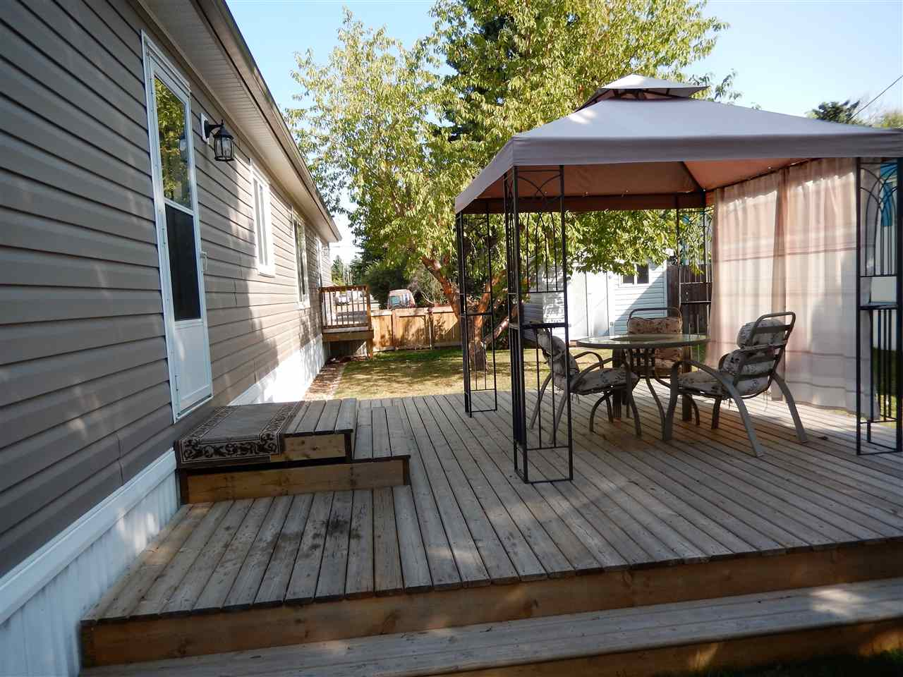 FREE LOT RENT TO END OF YEAR!!  JUST LIKE NEW and BACKING ONTO FIELD! Really LARGE FENCED YARD with plenty of MATURE TREES including CHERRY TREES..... Super private, LARGE DECK, 10x10 SHED & a 2ND SHED....definitely the BEST LOT IN MOBILE CITY! This 2015 home was moved in 2 yrs ago, so not only was the home new, but the fencing, deck, blocking, skirting & sheds were too! The home has been WELL CARED for by the seller's parents.  Beautiful KITCHEN with GORGEOUS cupboards, raised LUNCHBAR, STAINLESS APPL, & attractive VINYL flooring....HUGE LAUNDRY/UTILITY ROOM (plenty of storage).  The MASTR BEDR has a WALK-IN CLOSET & ENSUITE with large SOAKER TUB. At the other end is 2 more bedrs & FULL BATHR. Also transferrable WARRANTY.  The seller has installed SHUT VALVES under every sink. GAZEBO incl. Mobile City sits in the heart of Spruce Grove and is within walking distance of many amenities as well as the walking/bike trails system.