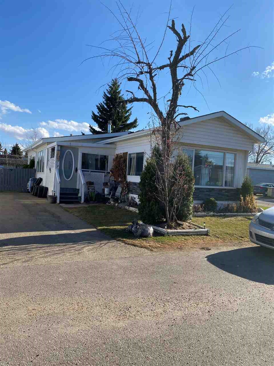 This mobile home is nicely updated and is an affordable living option. It features a fully fenced yard for a young child or pet plus an extra long driveway (48 ft.). Entering the enclosed entrance, you get a welcoming feeling. Step inside and imagine life in this 2 bedroom home. There is an additional formal dining room with vaulted ceilings and a second addition of a large room that is insulated and has it's own furnace. The living room is spacious and the kitchen has extra cabinetry plus a breakfast bar as your table space has been moved into the dining room. The 5 pce bathroom has double sinks and shares space with the laundry area. Both bedrooms are large, have 2 windows and the master has a walk in close.  WEST VIEW Village is well established and has a handy location close to Spruce Grove, West Edmonton, St. Albert and Industrial parks where you may work. Lot rental is $720 and your corner lot is larger than most. You should come compare this unit's features to a condo where you will have condo fees