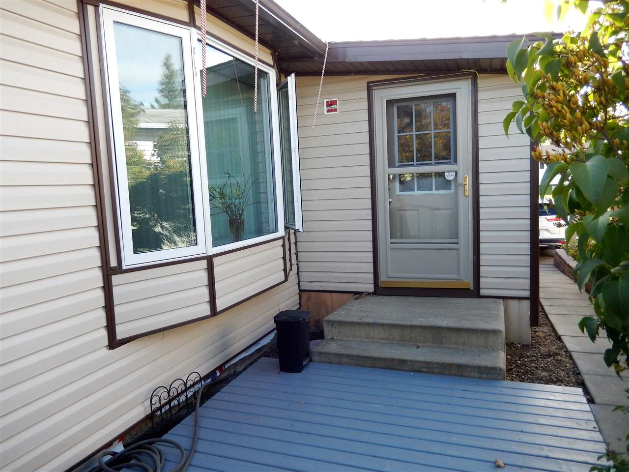This DOUBLE WIDE home has a UNIQUE LAYOUT and with the Addition, there is 1408 sq ft...Spacious Living Rm, Formal Dining Rm with GARDEN DOORS leading to the BACK DECK, GORGEOUS GALLEY KITCHEN (completely renod) & DINETTE area...MASTR BEDR has WALK THRU & WALK-IN CLOSETS, plus 2PCE ENSUITE...2 more bedrs & MAIN BATHR has LARGE SHOWER with SEAT. The home is all DRYWALLED & has beautiful BIG WINDOWS...the ADDITION is 20x8 ft (unheated) & serves as a PORCH & big STORAGE area. Over recent years this home has had a complete reno including: SHINGLES (2018), HWT (2018),  SOFFIT, FACIA, EAVESTROUGH, STRYOFOAM INSUL & WRAP (under siding), SKIRTING, SIDING, COMPLETE KITCHEN, ALL SHUT OFF VALVES, RENOD BATHRS, PAINT, BASEBOARD, FLOORING (no carpet), WINDOWS, WINDOW COVERINGS, FURNACE & ALL NEWER APPLIANCES. The PRIVATE YARD has a BIG DECK, raised FLOWER BEDS, SHED, TREES & SIDEWALKS on both sides. THIS HOME SITS ON CONCRETE PONY WALL AND HAS PILINGS UNDERNEATH.