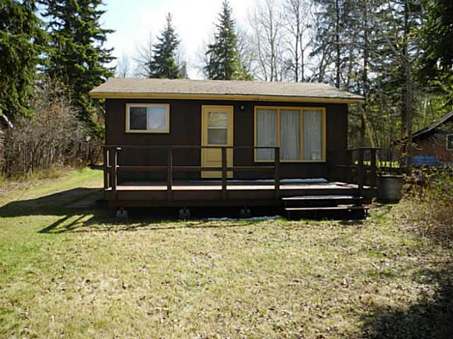 Original owner lakefront seasonal cottage. Nice two bedroom with eat in kitchen featuring wood cabinets, fridge and stove, side the spacious living room with large windows bringing in the natural light and lake views. Inside bathroom has a recirc toilet and water tank that feeds the sink. There is a second biffy in another building that houses a shower. There are two natural gas space heaters in the home for those chilly beginning and end of season nights. Great deck for entertaining and plenty of parking for RV, toys, etc. Large pull thru garage/boathouse measures 11.5 x 34 feet. Plenty of outbuildings for storage as well as a lakeside firepit. The lot is partially treed and a large sandy beach leads to the water. New shingles in 2006.
