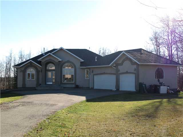 This beautiful walk-out hillside bungalow with triple attached garage is on 3 gorgeous acres and is only 15 minutes from the SE leg of Anthony Henday. Paved access all the way to this nicely treed acreage in Ministik Estates. Garage is heated with extensive cabinetry for storage. 12ft ceiling in LR. Pillars, arches, roman blinds and crown moulding in open great room. Formal Dining room and breakfast Nook. 6 Bedrooms and three (3) 5-piece Baths. Main floor Laundry. Raised breakfast bar. Both a raised deck out from Nook and Patio outside huge Family room. FR has valence lighting and a wet bar with cabinets and bar fridge. 1500 Gallon cistern is in mechanical room and conveniently located for refilling. New berber carpeting on lower level. Hardwood, laminate and ceramic tile throughout main floor. 3 sheds and a greenhouse. Just 2 kms south of Hwy 14.