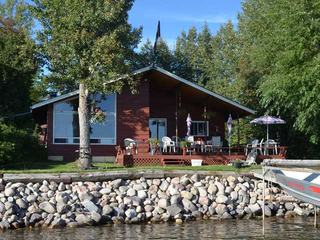 Wabamun Classic Lakefront! Lakefront cottage at Sherwin Beach. Vaulted ceilings, cedar and wood burning fireplace with gas lighter. There is a covered deck for shade. The lot is south facing where you capture sun from sunrise to sunset. Mature trees and covered deck provide shade throughout the day. Superior double detached garage with guest bunk house above and a 2 piece bath. There is a 229 ft well (2 years old) and 2 holding tanks for the home of 1500 gals and one for the garage is 1000 gals. The kitchen and dining room overlooks the lake. Bi-dishwasher assists. There is a loft, 3 large bedrooms and one 3 piece and one 4 piece bathroom. There is a skylight to bring in extra light. The property is in close proximity to Edmonton and 5km to the Town of Wabamun.