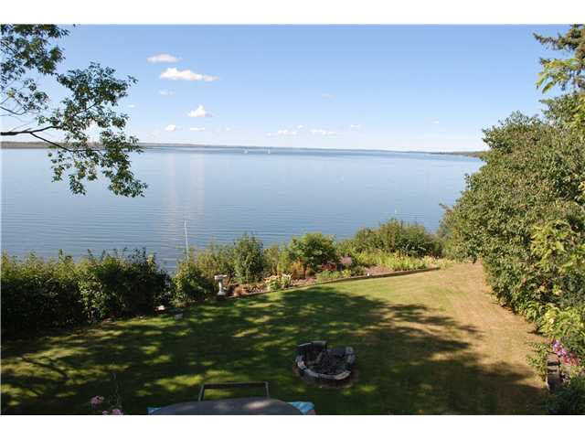 Year round WATERFRONT living on spectacular Lake Wabamun! Bright & open main floor with hardwood flooring, expansive lake views, living room with brick wood burning fireplace, bedroom, 3 piece bathroom & laundry room. Open kitchen with custom maple cabinets and breakfast nook with patio doors to front deck allow you to enjoy your morning coffee while taking in the breathtaking views. Upper level master suite with large windows and sitting area overlooking the lake, 2nd brick wood burning fireplace, and patio doors to private covered deck. 2 additional bedrooms and full bath complete the upper level. The unfinished basement with 8 ft. ceiling is the perfect way to give this home your own touch. Landscaped, low maintenance yard with plenty of mature trees for privacy & an outdoor hot tub to enjoy the amazing sunsets. Extras incl beach boathouse with rooftop deck, double detached garage w/ metal roof, RV parking, and security shutters. Located adjacent to Ironhead Golf & Country Club and 35 min to Edmonton.