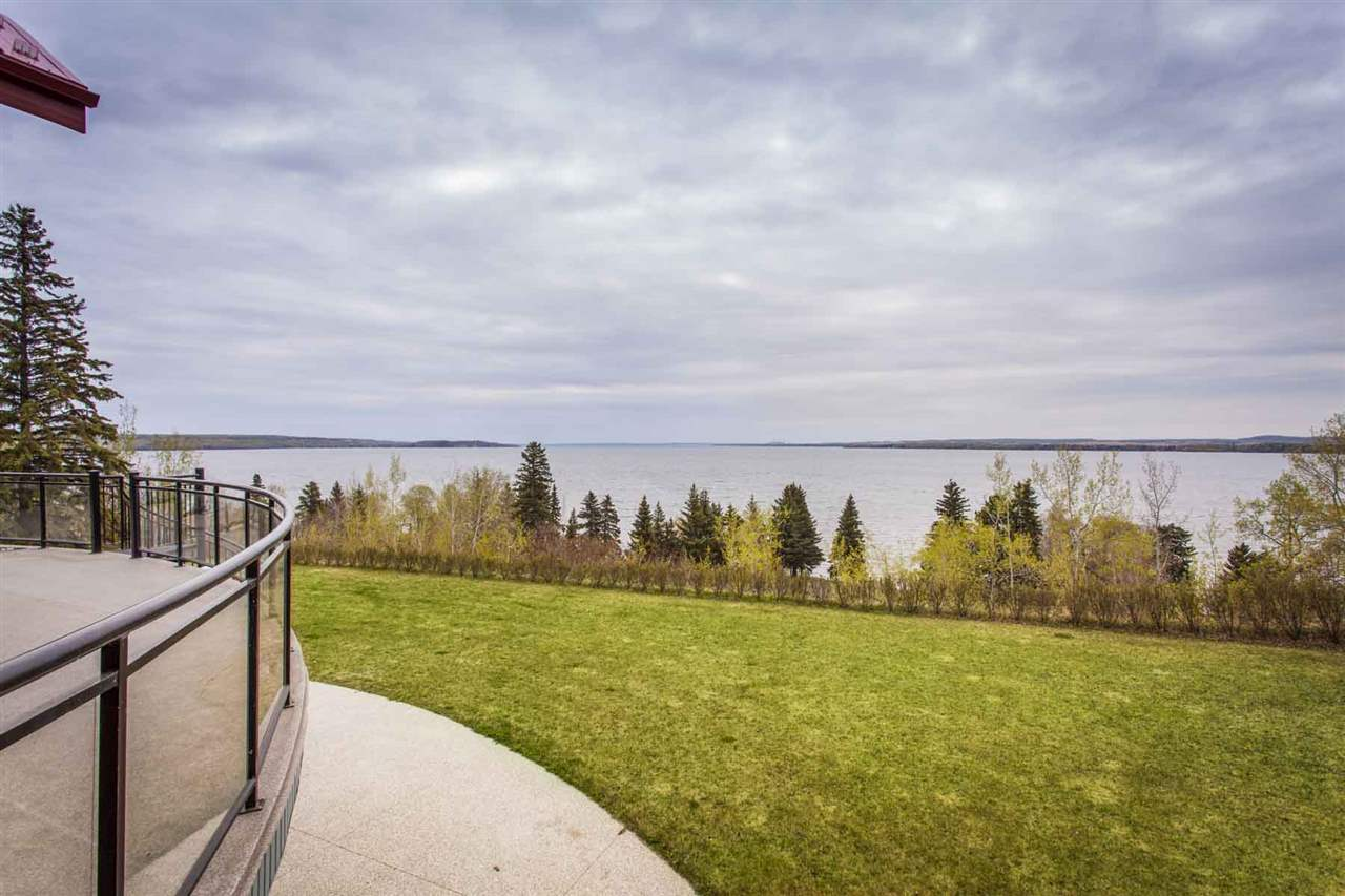 Boasting panoramic views and an abundance of natural light, this spectacular custom built home sits on 0.51 acres near the Summer Village of Seba Beach. Welcoming you into the home with views of Lake Wabamun is a great room with floor to ceiling windows, skylights, vaulted ceiling, and stone gas fireplace. Enjoy preparing meals and dining in a beautifully appointed kitchen with breakfast nook which opens to a family room with stone gas fireplace and picturesque views. Sitting on its own level with a private balcony and overlooking the rock garden with pond is the peaceful master with ensuite. The fully finished walk-out lower level features a private media room, 2 additional bedrooms, and a 2nd kitchen opening to a living room with stone gas fireplace. Located next to a park reserve, this spectacular 3 bedroom home offers deck access from every room, and the beautifully landscaped yard boasts over 200 ft. of unobstructed lake views.