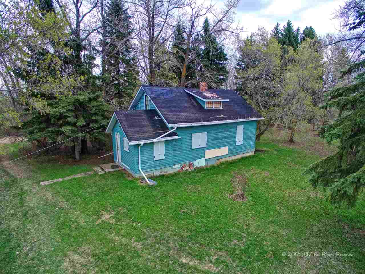 Bordering the town of Bruderheim is this 6 acre parcel of land with an older three bedroom home and several out buildings.