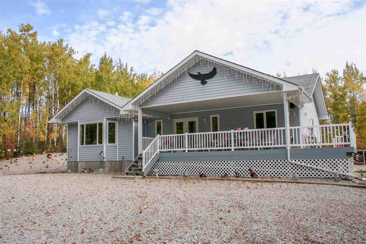 Just minutes from Alberta Beach and Onoway lies this wooded oasis on 3+ acres, with an immaculate 1485 sqft home nestled amongst the trees! A tree-lined driveway welcomes you to the home and peaceful forest views are enjoyed from a partially covered wrap-around deck with maintenance-free railing! This 3 bedroom, 3 bath bungalow is spotless and shows pride of ownership throughout, with ideal features: hardwood, tile, and laminate on the main level, vaulted ceiling, rounded corners, very spacious kitchen with abundant cabinetry and pots & pans drawers, garden door to deck from the dining room, and gas fireplace with art niche above! The master bedroom has his & hers closets and a 3-pce ensuite! The unfinished basement is warm with in-floor heating, has bathroom roughed in, in addition to hot water heating system with boiler! Parking and outdoor storage are a dream with the triple detached garage plus 30x50 quadruple shed with covered RV parking and two more sheds! Perfection and privacy!