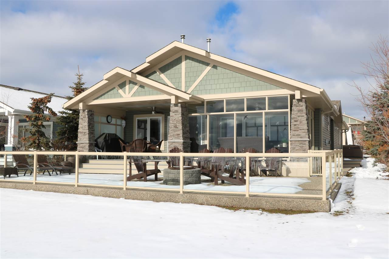 SOUGHT AFTER WATERFRONT HOME!! This amazing 3 plus 1 bedroom bungalow is located on the north shore of Lac Ste Anne. Large tile and custom FUMED wood flooring blanket this gem as you traverse thru the wide open plan. Loads of wood cabinets capped with Quartzite and stainless appliances complete the kitchen which overlooks the massive lakeside dining room. A stone F/P and huge South facing windows make the living room bright and warm. Solar tubes flood the halls with light as you make your way to the 3 spacious bedrooms in the main house. There is a guest house with a 4th bedroom and 3rd bathroom that is fully self contained. The covered deck is partially glassed in and features B/I gas heaters and gas to BBQ. Exposed pad with firepit and glass rail make way to the shoreline. New central ac. Double heated garage with cabinets, storage shed and hot tub pad as well. There is RV parking stall and a 24x30 finished warehouse available for sale also. Pool, rec centre, private marina and RESORT lifestyle awaits!!