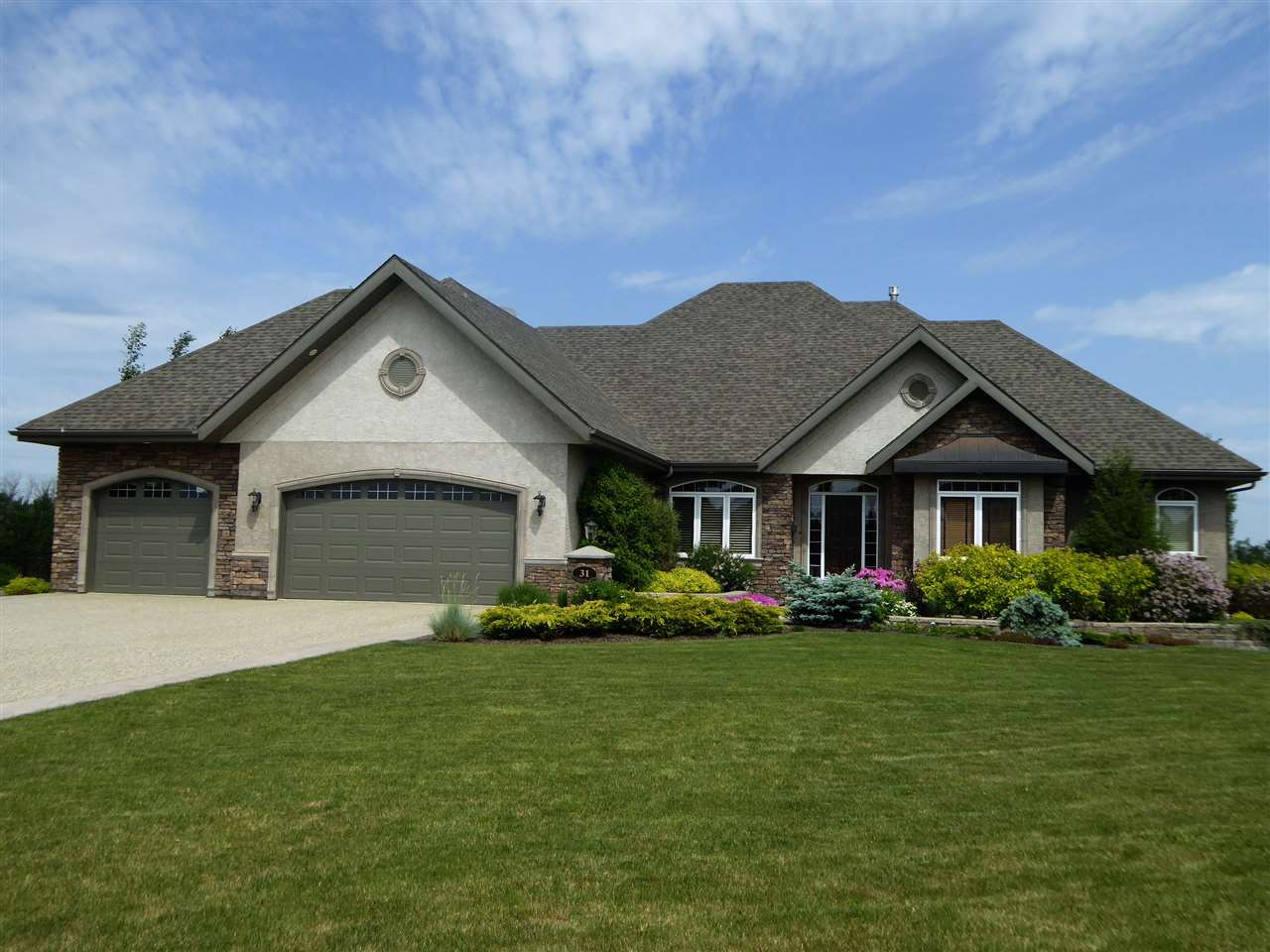 Beautiful Executive 2500 sq.ft walk-out bungalow on quiet cul-de-sac in Countryside Ravines features high quality custom finishings & extensive millwork. The Great room showcases a dbl sided stone F/P & large windows. Gourmet kitchen w/ hearth style BI cooktop, BI ovens, walk-through pantry & granite island w/breakfast bar opens to a spacious dinette area. The grand Master suite has a gas F/P, double WI closets, 5 pc ensuite w/Bain-Ultra soaker tub and WI shower. Expansive windows in sitting area w/private deck access. Completing the main floor w/imported solid cork flooring are a study, formal dining room, powder room, bedroom w/BI window seat, 4-pc bath, laundry & mud room. A curved staircase opens to a spacious media/games area w/wet-bar, 2 addt?l bedrooms, 4-pc bath, craft room, wine room and state-of-the-art fitness room. O/S triple garage w/floor drain is f/f and heated. Gorgeous yard w/ multiple hard scapes incl water-feature, hot tub, mature trees & BI irrigation. Only 2 paved minutes to Edm.