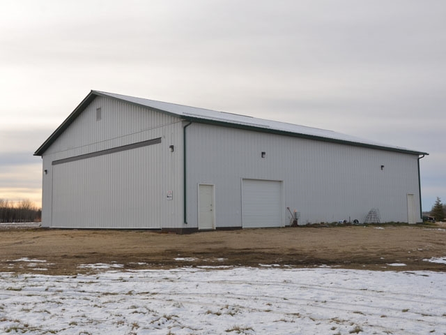 Exceptional 50'x70' Highwall shop with living quarters on 3.16 acres only 3.25 miles from Barrhead and a stones throw from Barrheads Airport and Provincially recognized golf course. Completely finished inside and out featuring in floor heating system. Special 40'x14' hydraulic opening overhead door large enough for Airplane access, highway tractors or any equipment plus convenient 8'x9' car door. Remarkable location with close proximity to town and only a quarter mile to pavement. This is a property and building with extensive ability now and exceptional potential for the future to build your home and yard site as you desire.
