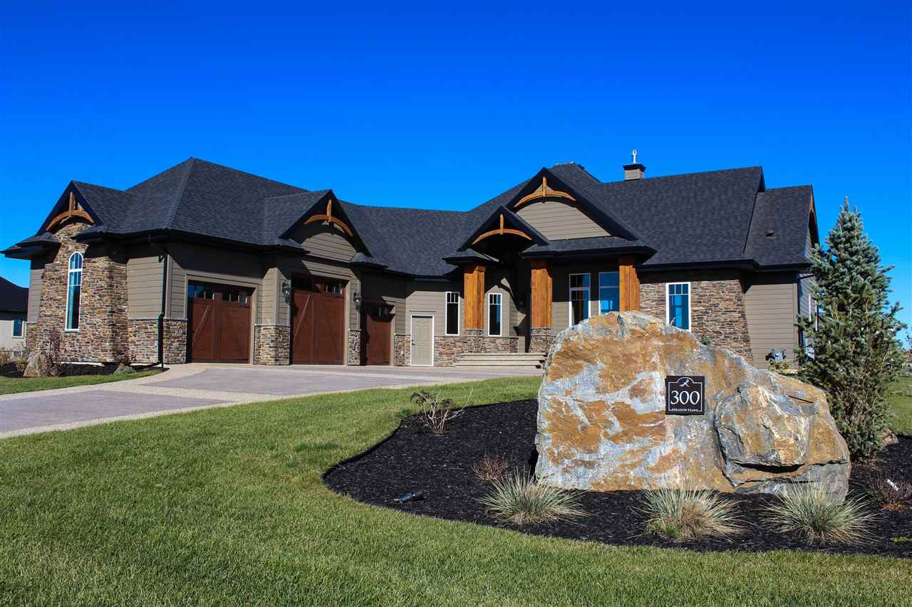 Spectacular custom built bungalow by Casa Bella Construction with over 4600sq of top quality finished living space & a 1217sqft 3 car heated garage. From the time you pull up it is evident this is a well built home. Hardie Plank siding accented with stacked stone and wood arches. Curved stamped & exposed concrete driveway & the professionally designed & landscaped lot backing a park.Once you enter you will be immediately impressed with the wide open plan, gorgeous hickory cabinets, huge granite island & backsplash, top quality stainless appliances overlooking the great room and a floor to ceiling stone faced double sided fireplace, hardwood floors, dining room with tile floor & stacked ceiling. Master suite with sitting area, door to deck, barn door to 5 pce. en suite & massive walk through closet leading to laundry. Addiditonal bedroom and den on main floor. Fully developed lower level with Jack and Jill bedrooms, rec room with bar area, media room + fireplace.