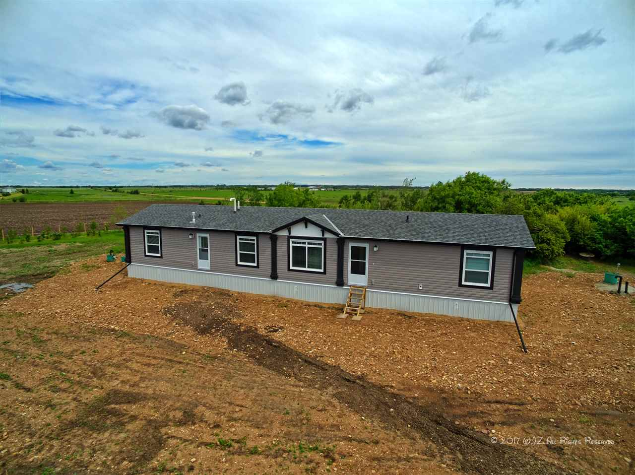 Located minutes east of Chipman and less then 2 miles from Hiway 15 is this 80 acre parcel of land with a 2015 Bradford model built by Triple M Housing modular home offering 1520 square feet of living space.  The home features a gorgeous country style  kitchen with an abundance of cupboards, counters space, huge island, spacious eating area and a  huge living room area. The master bedroom with a 5 piece en suite is located at one end of the home.  The three bedrooms and a 4 piece bathroom are located on the opposite end.  Laminate flooring through out the home other than the master bedroom having carpet compliments the property. The 2800 gallon cistern and the septic system( tank and open discharge) are newly installed.
